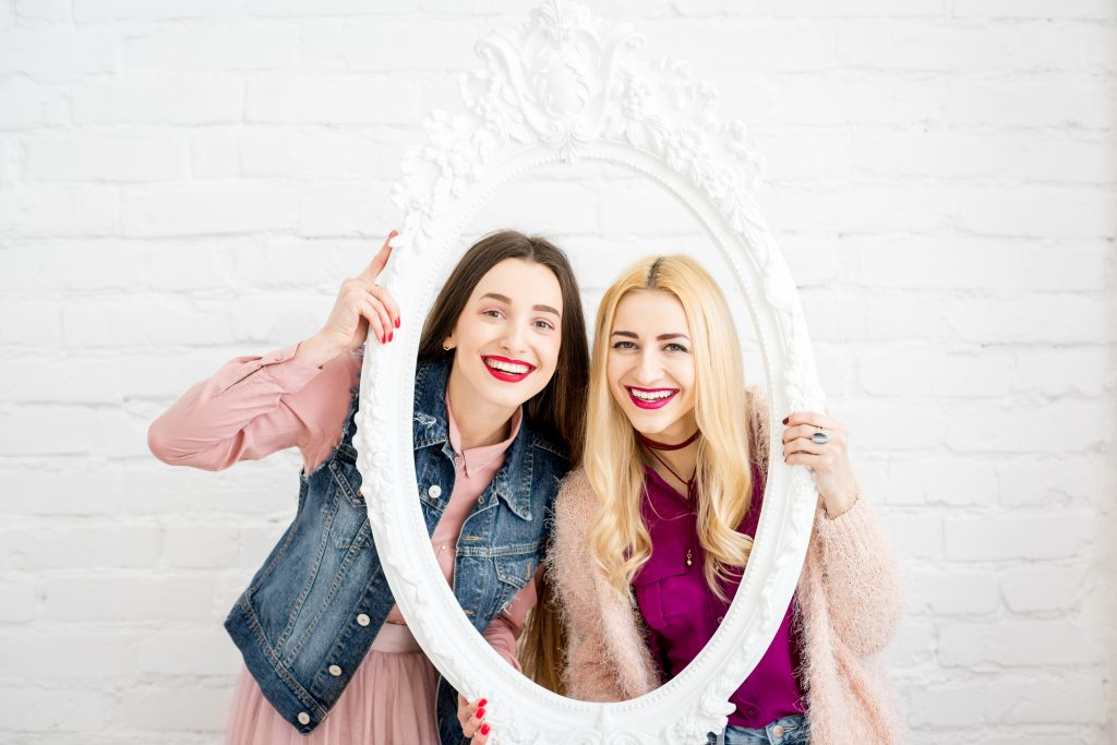 Two Women Posing In Photo Booth For Their Company Event